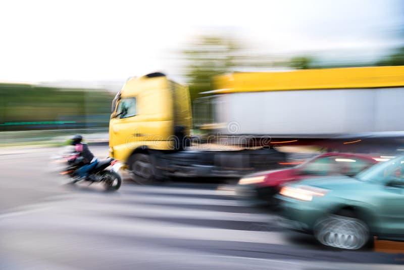 与摩托车骑士和卡车的危险城市交通情况 免版税库存照片