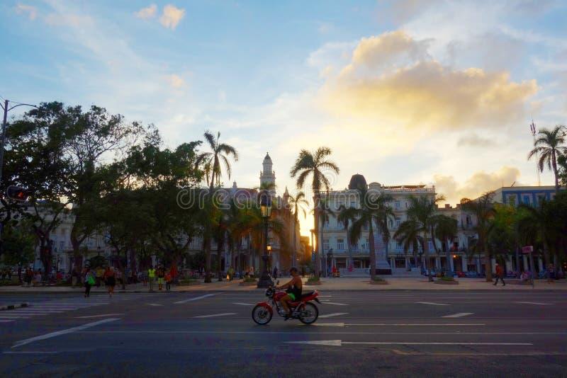 与摩托车,哈瓦那,古巴的五颜六色的殖民地大厦 免版税库存照片