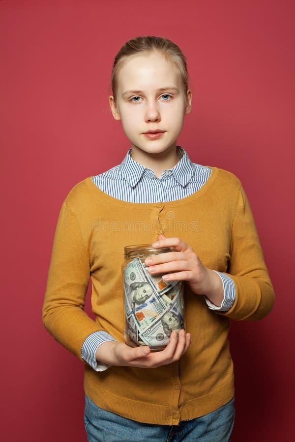 与攒钱的孩子在玻璃瓶子 免版税库存图片