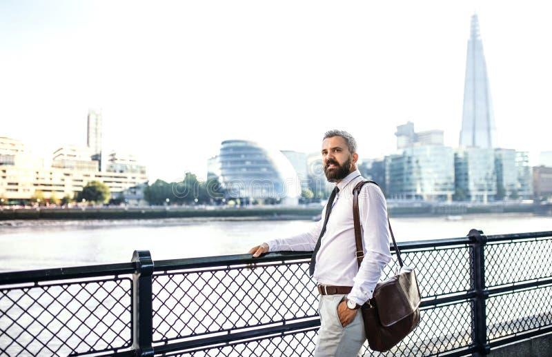 与支持河的膝上型计算机袋子的行家商人在伦敦 免版税库存照片