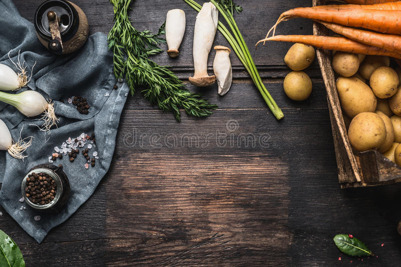 与收获菜、绿色、土豆和蘑菇的秋天季节性烹调成份在黑暗的土气木背景, 免版税库存图片