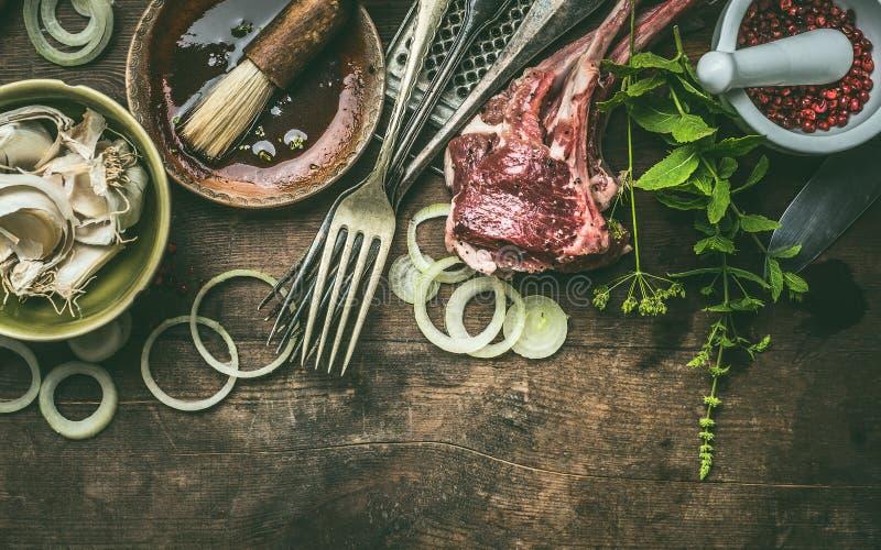 与放在架子上的羊羔的格栅准备与新调味料、BBQ简单的卤汁和厨房用具的在土气木背景 库存照片