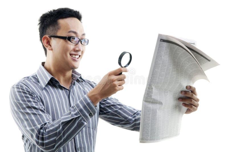 与放大器的亚洲人读书报纸 库存图片