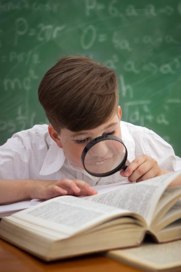 与放大器的小的学生男孩阅读书 库存图片