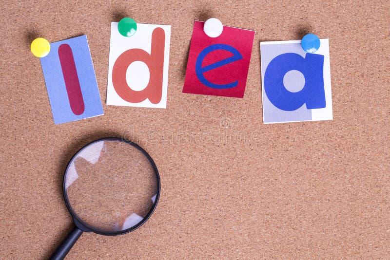 与放大镜的五颜六色的纸词想法在黄柏板 免版税库存照片