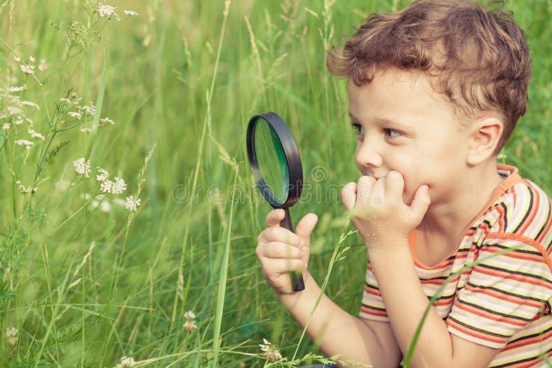 与放大镜的愉快的小男孩探索的自然 免版税库存图片