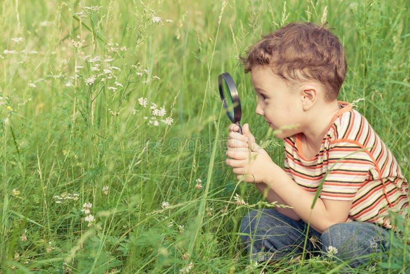 与放大镜的愉快的小男孩探索的自然 库存照片