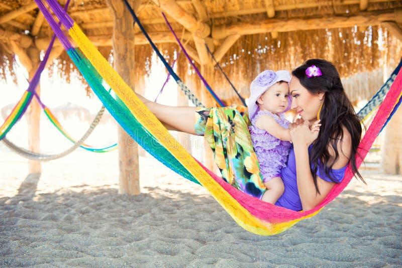 与放松在吊床的逗人喜爱的女儿的愉快的时髦的家庭在晚上太阳光的暑假在海滩 行家夫妇w 免版税库存图片
