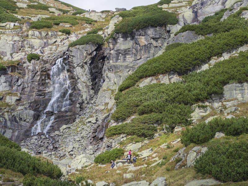 与放松旅游人民和徒步旅行者,夏天好日子,Strbske普莱索,斯洛伐克的Skok瀑布高Tatras山 免版税库存图片