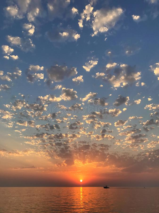 与放热太阳光芒、云彩和风平浪静水的美好的风景日落海景 库存图片