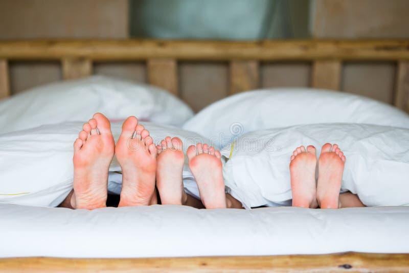 与放置在与今后他们的脚的床上的两个孩子的家庭 图库摄影