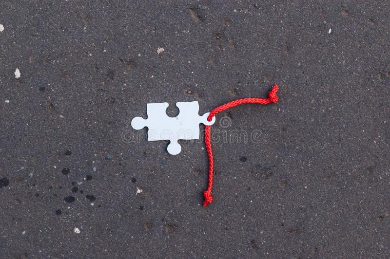 与放置在柏油碎石地面的红色鞋带的缺掉曲线锯的片断 免版税库存照片