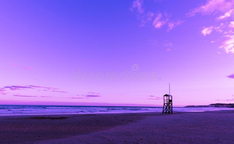 与救生员木塔的紫外海滩日出 库存图片