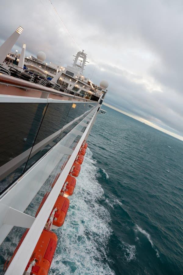 与救生艇的海巡航划线员在多云天气的海洋 侧视图 库存照片