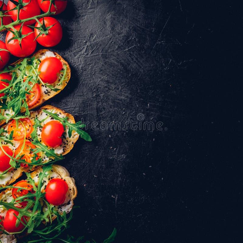 与敬酒的长方形宝石、酸奶干酪和新鲜的有机西红柿的Crostini 老黑织地不很细背景 烹调意大利语的食品成分 顶层 库存图片