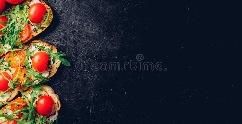 与敬酒的长方形宝石、酸奶干酪和新鲜的有机西红柿的Crostini 老黑织地不很细背景 烹调意大利语的食品成分 顶层 免版税库存照片