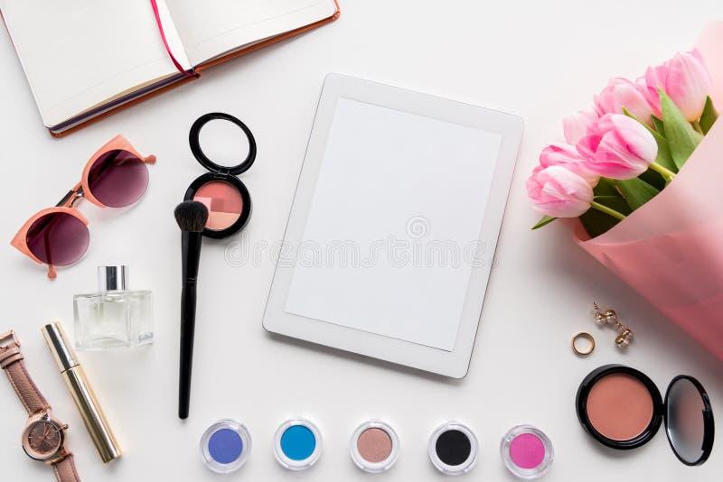 与数字式片剂、各种各样的化妆用品、桃红色郁金香辅助部件和花束的平的位置  库存照片