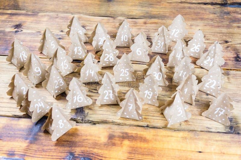 与数字的手工制造圣诞节出现日历圣诞树牛皮纸在木背景中 免版税库存照片
