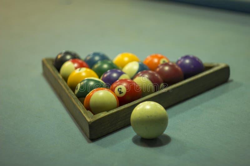 与数字的被弄脏的多彩多姿的撞球在一张蓝色布料桌上的一座木金字塔在一个白色球旁边 免版税库存图片