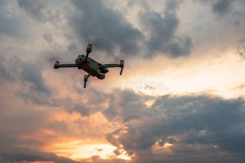 与数码相机飞行的寄生虫quadcopter在日落 库存照片