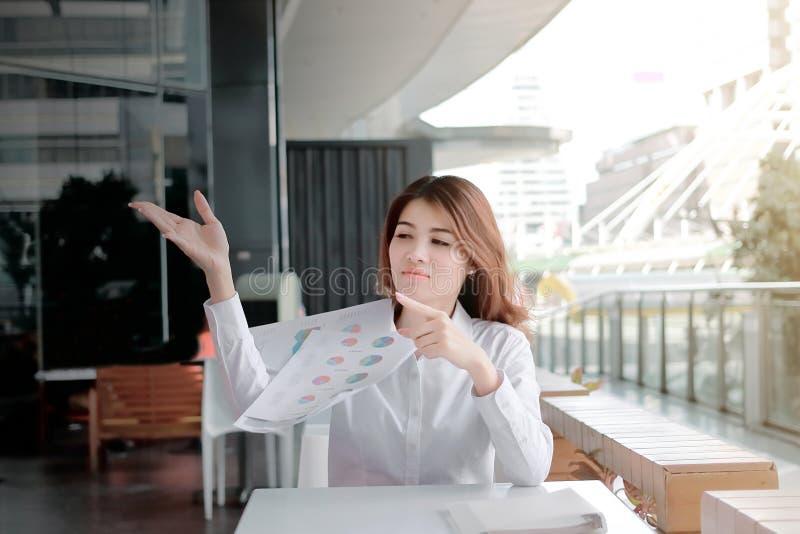 与文书工作的沮丧的被注重的年轻亚洲在书桌上的事务或图在办公室 免版税图库摄影