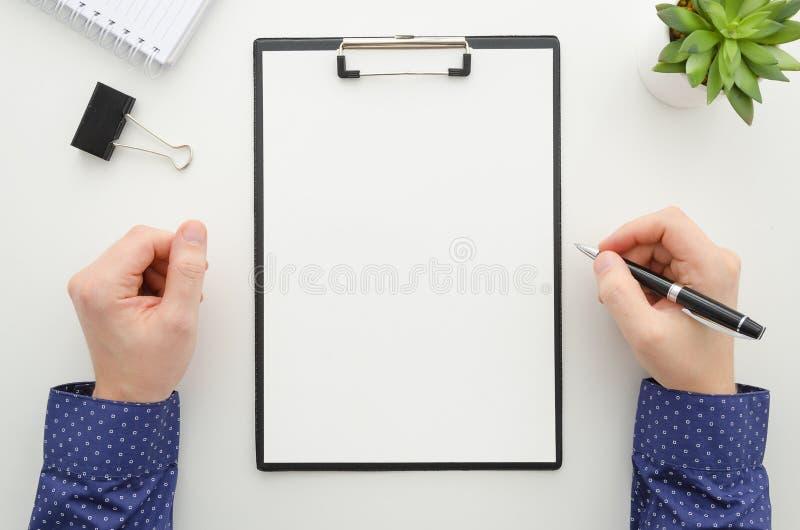 与文件一起使用和使用一个手机的商人 剪贴板大模型模板文书工作,财政报告 库存图片