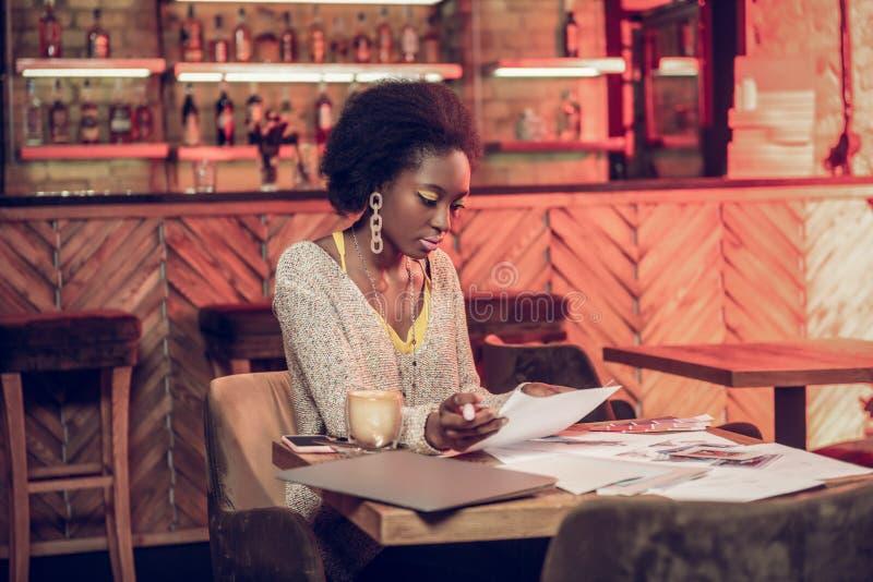 与文件的关心的流行nice-looking非洲的女性工作在自助食堂 库存图片