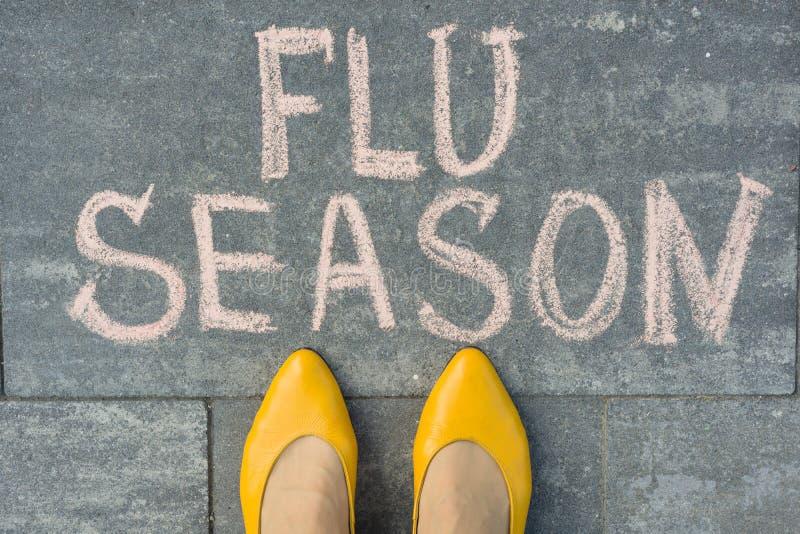 与文本在灰色边路写的流感季节的女性脚 库存图片