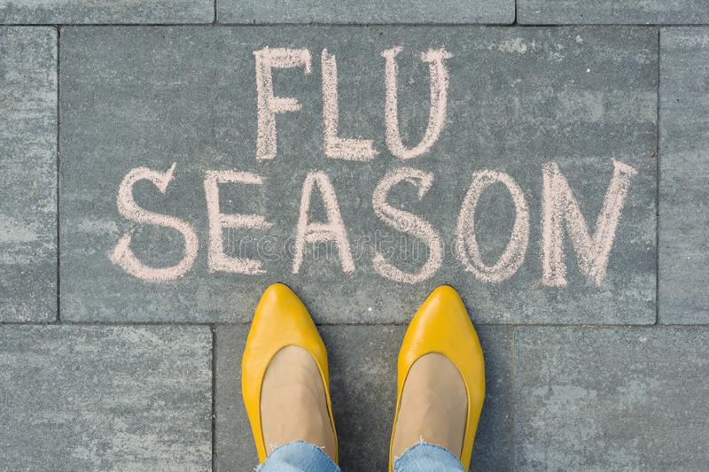 与文本在灰色边路写的流感季节的女性脚 免版税库存照片