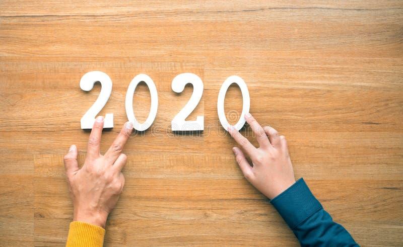 与文本数字和人的手的2020个新年庆祝概念在木背景 免版税库存照片