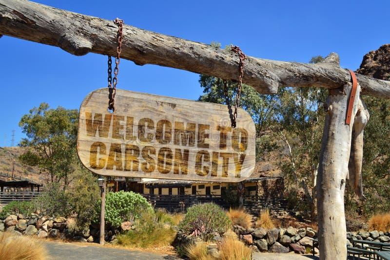 与文本欢迎的老木牌向卡森市 垂悬在分支 免版税图库摄影