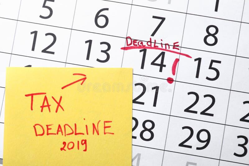 与文本税最后期限的纸板料在日历与明显日期 库存照片