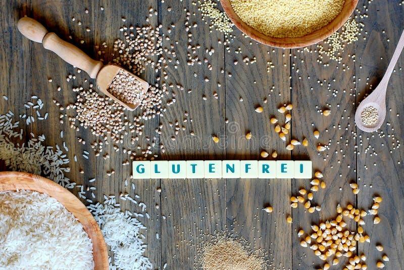 与文本面筋的面筋免费谷物玉米、米、荞麦、奎奴亚藜、小米和白苋在灰色木bac的德语释放 库存图片
