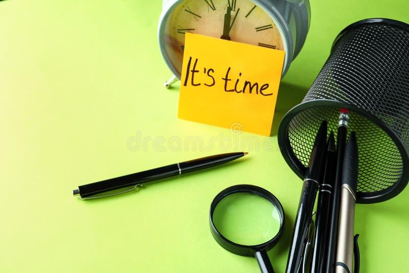 与文本IT \'S时间、文具和闹钟的纸板料在颜色表上 r 库存图片