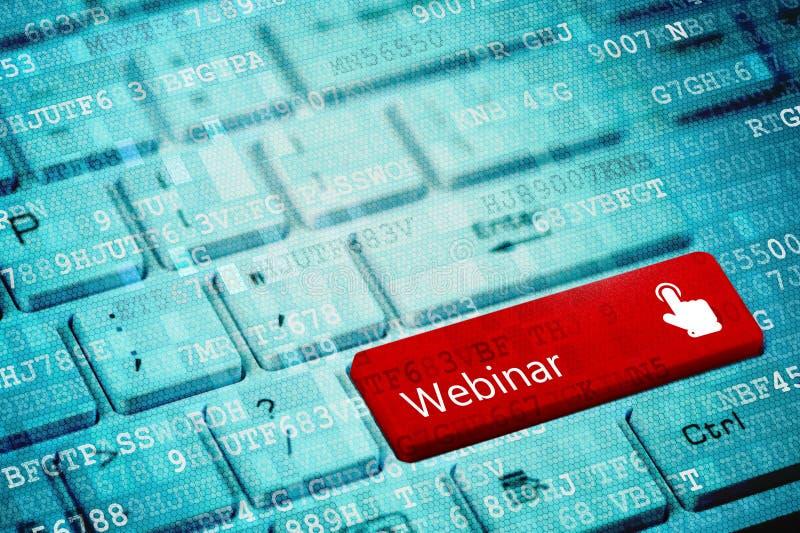 与文本Webinar的红色钥匙和手在蓝色数字式膝上型计算机键盘的游标象 库存照片