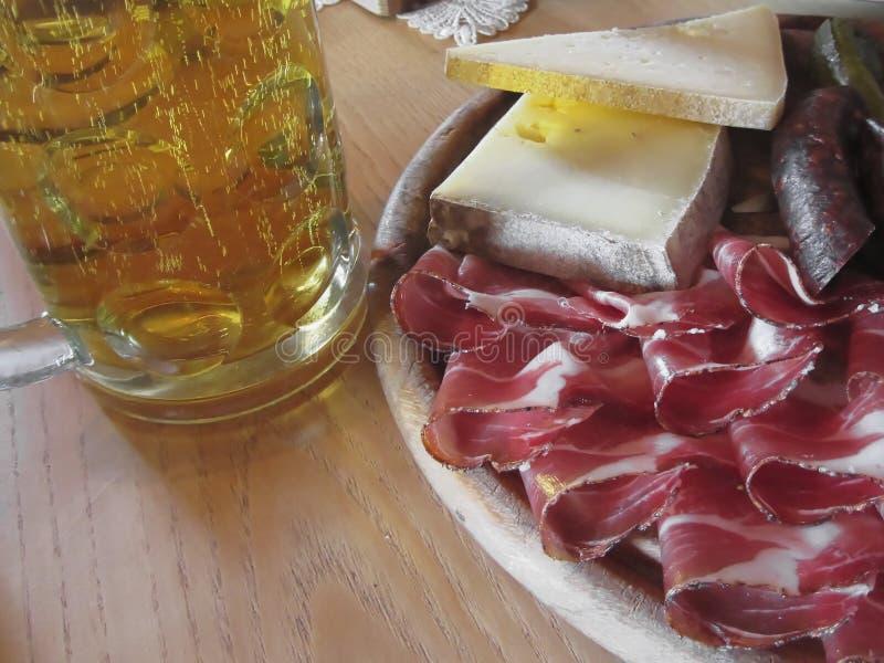 与斑点、山乳酪、熏制的香肠和一个冷的杯子的典型的南Tyrolean快餐低度黄啤酒 库存照片
