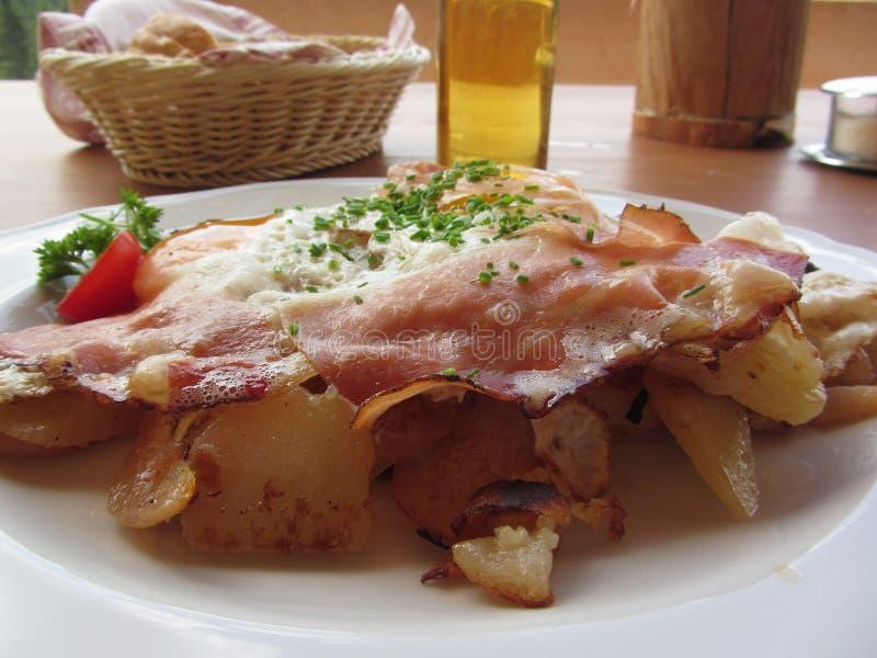 与斑点、荷包蛋、土豆和香葱的典型的南Tyrolean盘 免版税库存照片