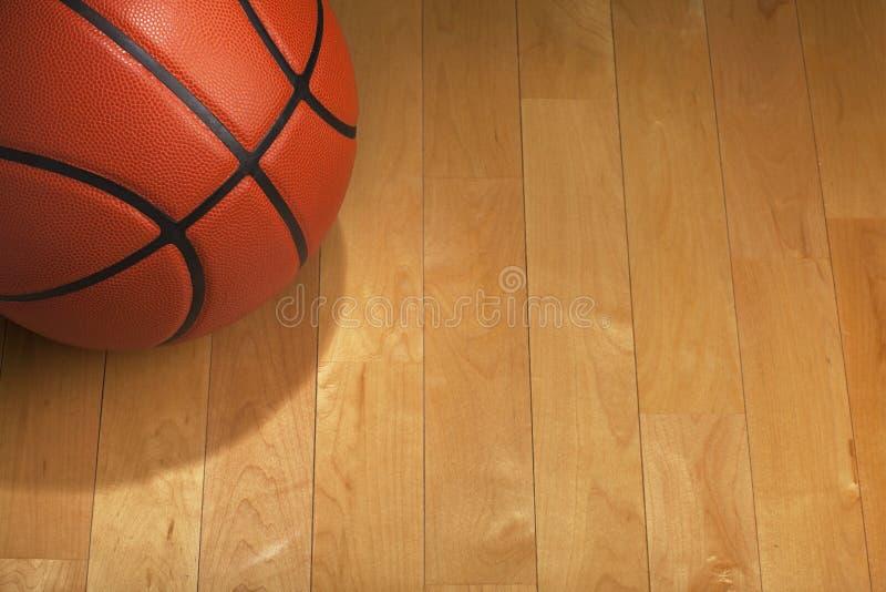 与斑点照明设备的篮球在木健身房地板上 免版税图库摄影