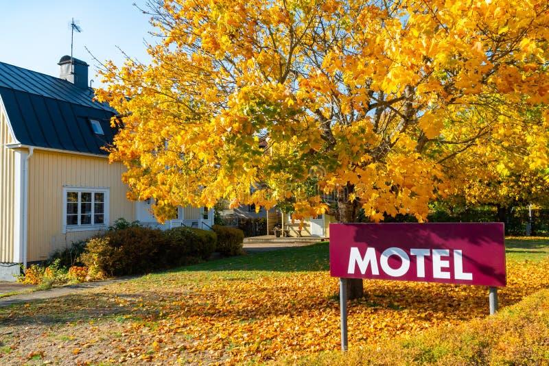 与斯堪的纳维亚房子和秋天树的汽车旅馆标志在背景 免版税库存照片