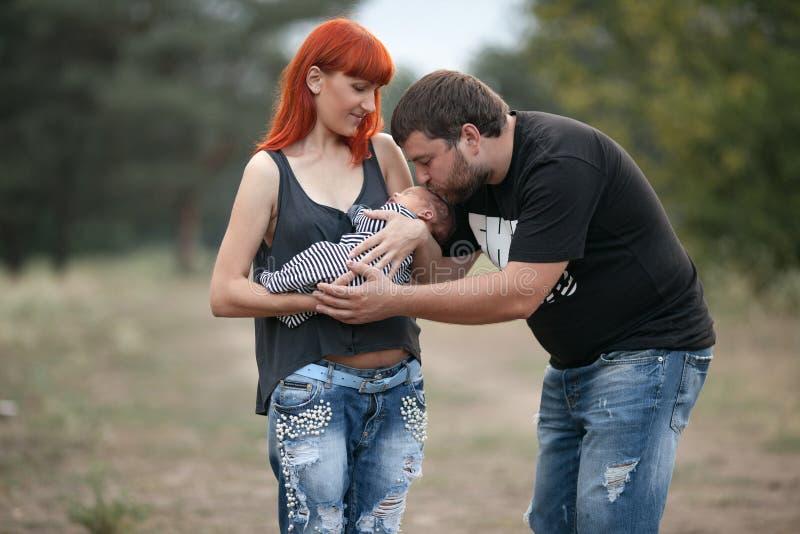 与新出生的婴孩的愉快的年轻家庭步行的在公园 库存图片