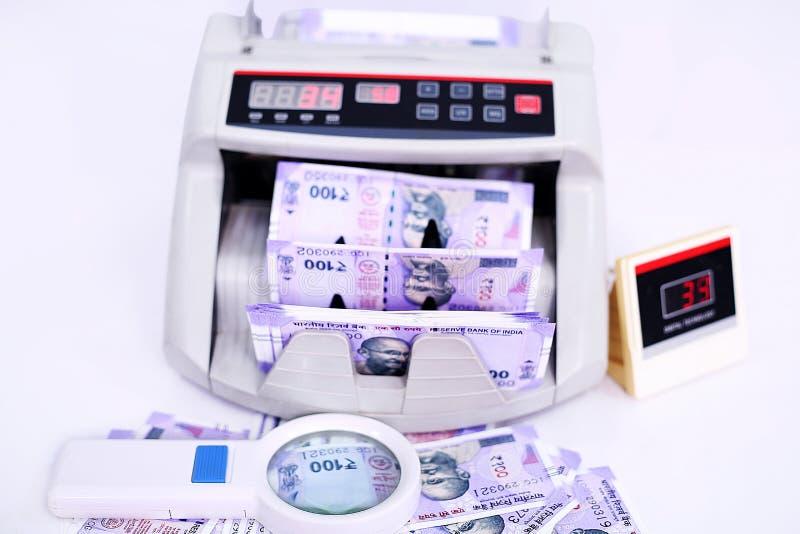 与新的100卢比的电子货币柜台笔记和放大镜 免版税库存照片