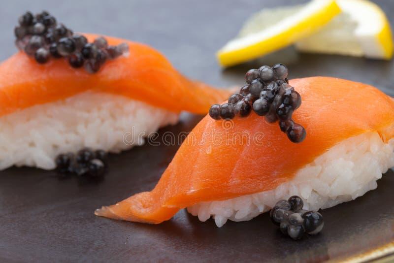 与新鲜的三文鱼和黑鱼子酱的Nigiri寿司 库存照片