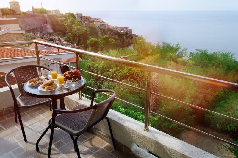 与新鲜的早餐的表服务在大阳台 免版税图库摄影