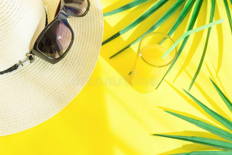 与新鲜的柑橘热带水果汁棕榈叶的端庄的妇女辅助部件帽子太阳镜高玻璃在黄色背景 晒裂 免版税库存图片