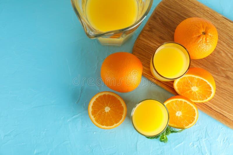与新鲜的橙汁过去的构成在玻璃器皿、薄菏和切板用桔子在颜色背景,顶视图 免版税库存图片