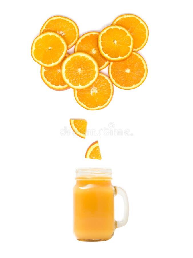 与新鲜的橙汁过去的玻璃站立在白色背景的许多橙色切片下 免版税库存图片