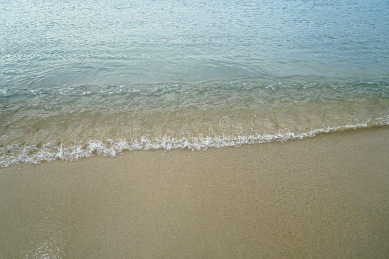 与新鲜的海水的软的淡色干净的沙滩和白色泡沫似的波浪排行背景和copyspace在Ornos岸 免版税库存照片