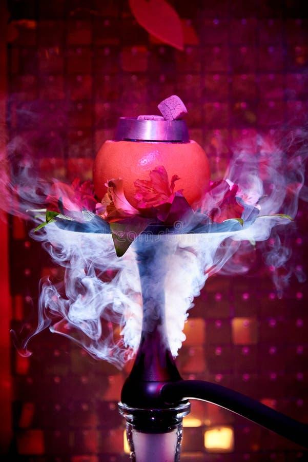 与新鲜的百合的柑橘水烟筒在烟云 免版税库存图片