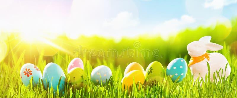 与新鲜的绿草和太阳的复活节彩蛋 免版税库存图片