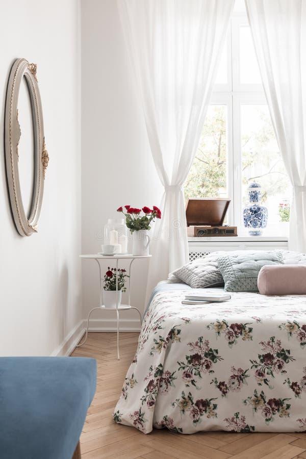 与新鲜的英国兰开斯特家族族徽、蜡烛和咖啡杯的白色床头柜 免版税库存照片